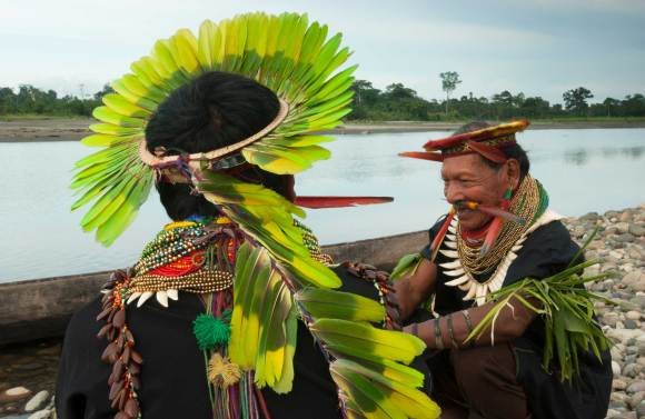 Cofan native people wear parrot feathers on their heads while speaking with each other. Photograph by conservation photographer and cultural photographer Pete Oxford.