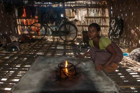 a Mising woman stokes a fire in her house. Photo by indigenous person photographer Pete Oxford.