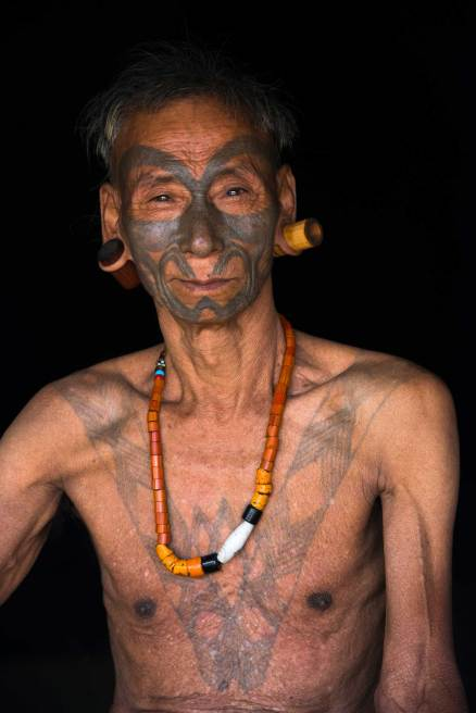 A Konyak Naga tattooed headhunter poses for a photo. Photograph by conservation photographer and cultural photographer Pete Oxford.