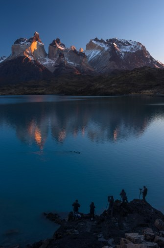 Photographers are silhouetted in from of Lake Pehoe in Torres del Paine National Park. Photo by travel photographer and conservation photographer Pete Oxford.