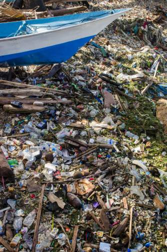 A huge amount of beach trash is shown underneath a small boat on the beach. Photo by conservation photographer Pete Oxford.