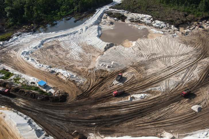 Countless tire tracks are shown in the dirt and sand of a gold mining site. Photo by conservation photographer Pete Oxford.