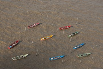 Multicolored fishing boats float tied up in the water. Photo by aerial photographer Pete Oxford.