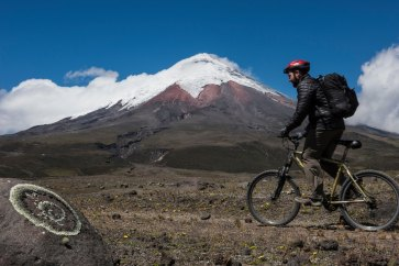 A cyclist rides past Cotopaxi Volcano. Photo by travel photographer and conservation photographer Pete Oxford.