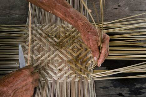 A man shows the process for weaving split cane. Photograph by indigenous person photographer Pete Oxford.