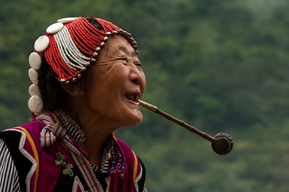 A bBlack Lisu woman smiles while holding a pipe in her mouth. Photograph by indigenous people photographer Pete Oxford.