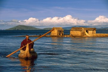 A man paddles a reed canoe on Lake Titicaca with a floating island in the background. Photograph by indigenous people photographer Pete Oxford
