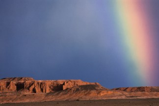 The Flaming Cliffs in Mongolia are shown with a rainbow in the background. Photo by landscape photographer Pete Oxford.