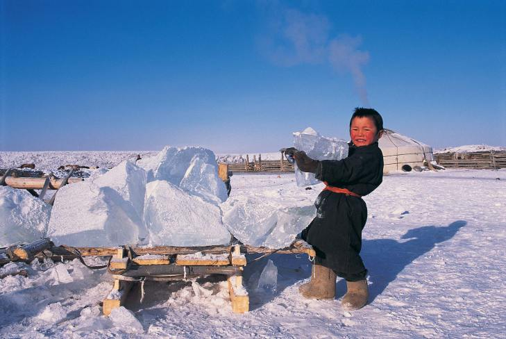 A Darkhad boy fetches ice. Nearby is a ger. Photo by travel photographer and conservation photographer Pete Oxford.