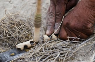 A Kalahari bushman is shown trying to make fire by hand. Photo by indigenous person photographer Pete Oxford.