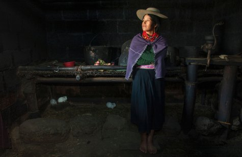 A Salasaca Indian poses in a home while wearing traditional dress. Photo by indigenous person photographer Pete Oxford.