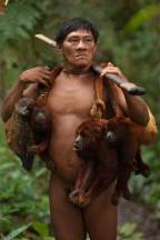 A native Huaorani hunter stands with the catch from his latest hunt in Yasuni National Park. Photo by conservation photographer and cultural photographer Pete Oxford.