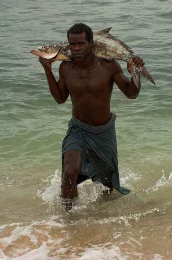 A Vezo fisherman exits the water with a large fish draped across his shoulders. Photo by indigenous person photographer Pete Oxford.