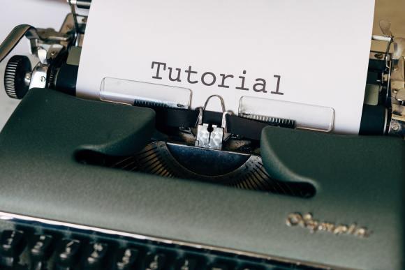 """Coverbild für """"Tutorials in WordPress schreiben"""": Eine mechanische Schreibmaschine mit einem eingespannten Blatt Papier auf dem groß """"Tutorial"""" steht."""