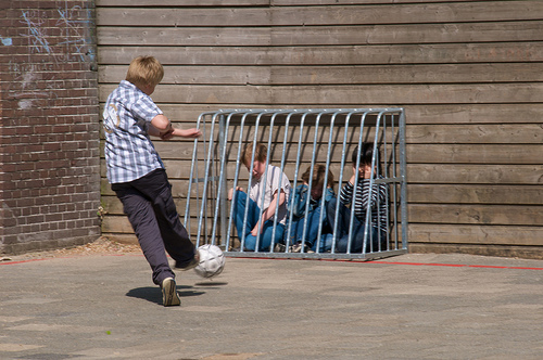 Large buy kicks socccer ball at younger boys cowering in a cage.