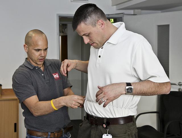 A man has his waist measured.