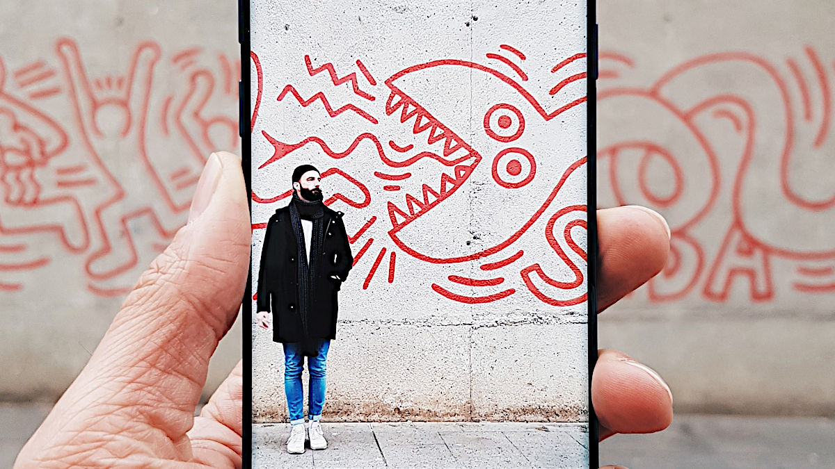 A man in front of a wall shown on a phone screen
