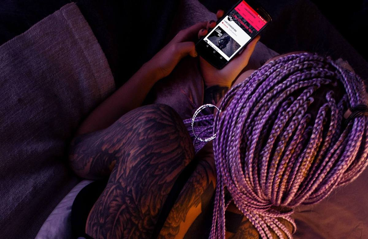 Black woman with braided hair using a smartphone