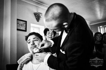 Documentary wedding photographer groom being shaved