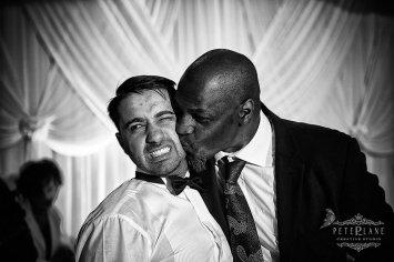 Documentary wedding photographer London a guest kissing the groom