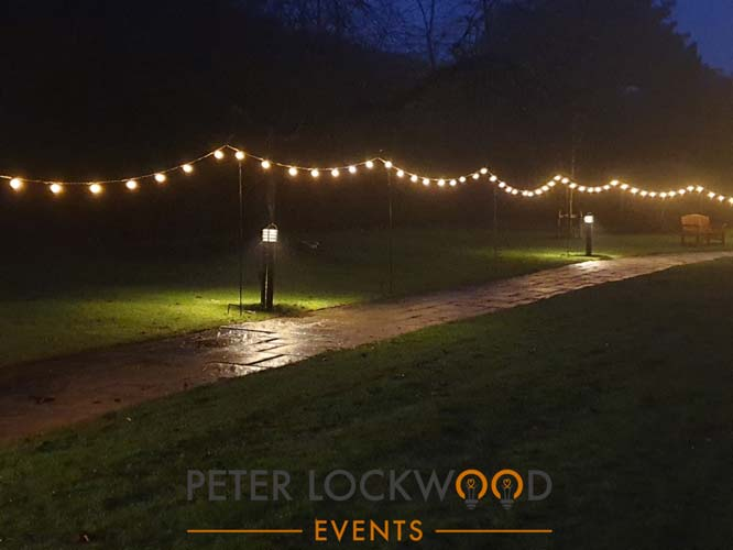 shepherd hooks and festoon lights lighting the way