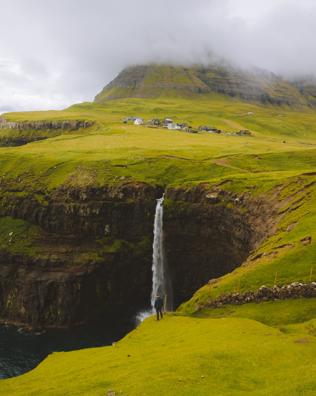 man standing on cliff watching punch bowl waterfalls