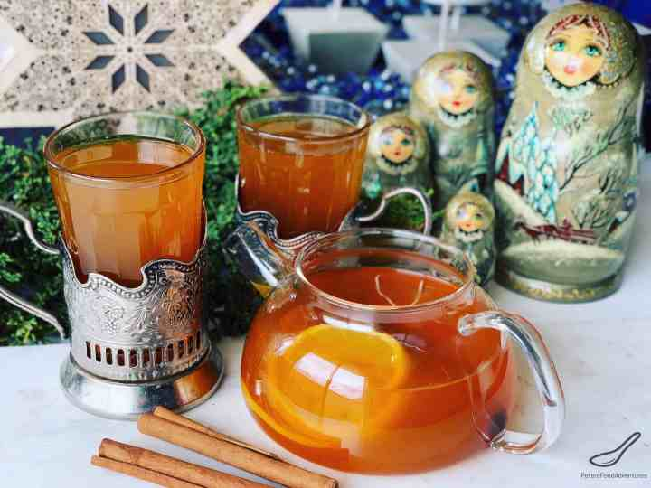 Russian Tea in a glass teapot served with Russian tea glasses. Placed on a table with cinnamon sticks and Russian nesting dolls