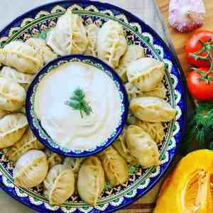 Manti (Манты) on a round Uzbek platter served with sour cream