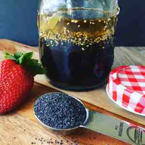 Jar of Poppy Seed Salad Dressing with a spoon of Poppy Seeds and Strawberries