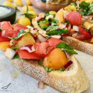 The secret to making a delicious Summer Bruschetta is to use garden fresh ripe tomatoes. It's so easy to make, jam packed with flavour from garlic, onions basil and balsamic vinegar, This is the best bruschetta I've eaten! Summertime Bruschetta with Tomato & Basil