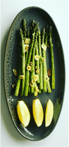 Top down view ofAsparagus on a platter garnished with lemon wedges