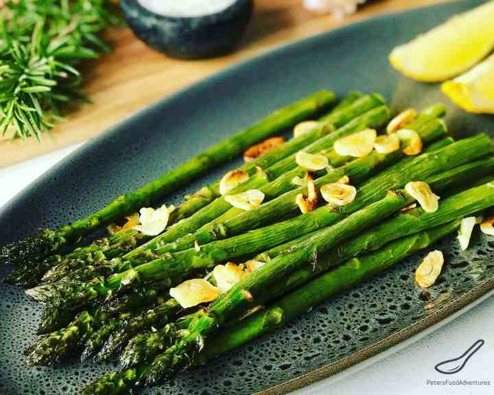 Roasted Asparagus on a platter with fresh rosemary and lemon slices