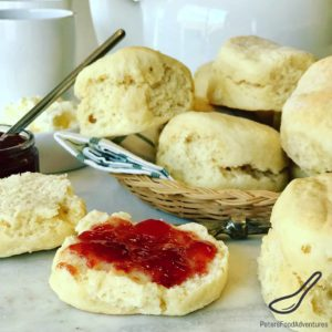 A basket of scones on a breakfast table, spread with strawberry jam.