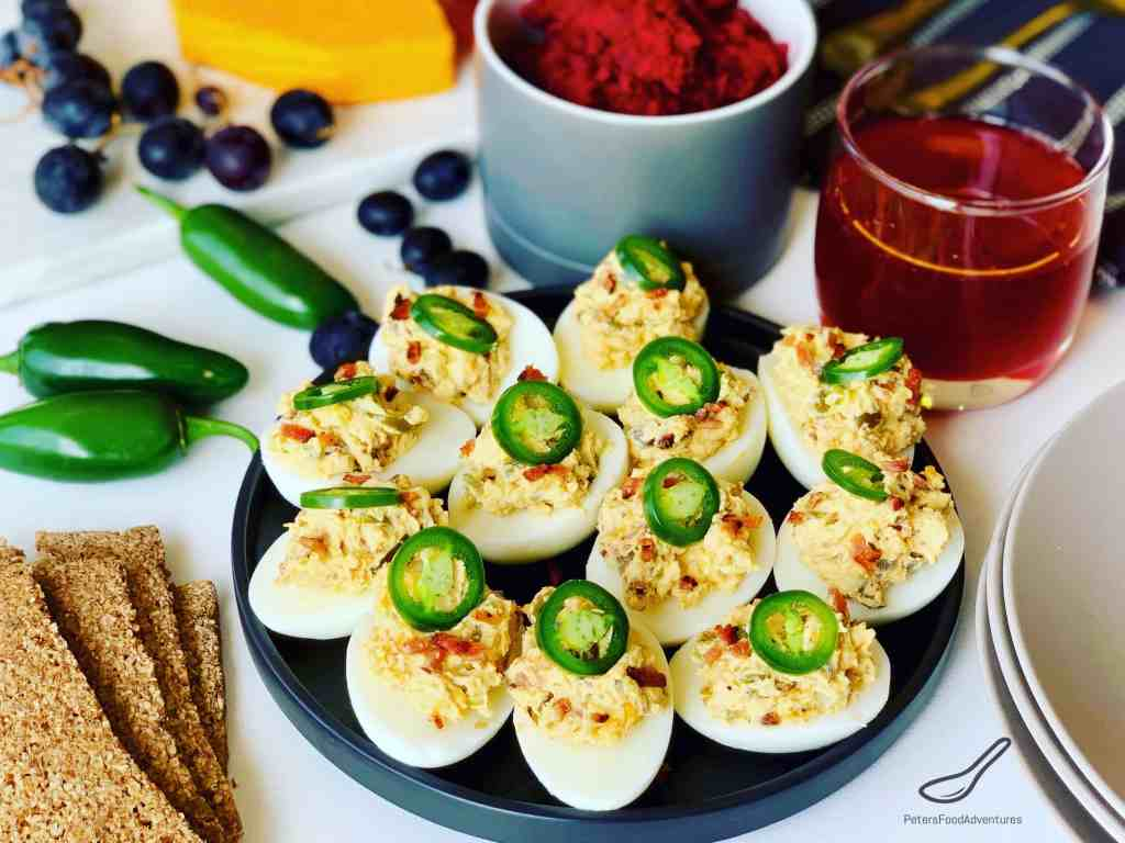 Jalapeno Popper Deviled Eggs served on a plate with appetisers, cheese and a glass of juice