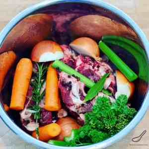 uncooked vegetables and bones in a pot