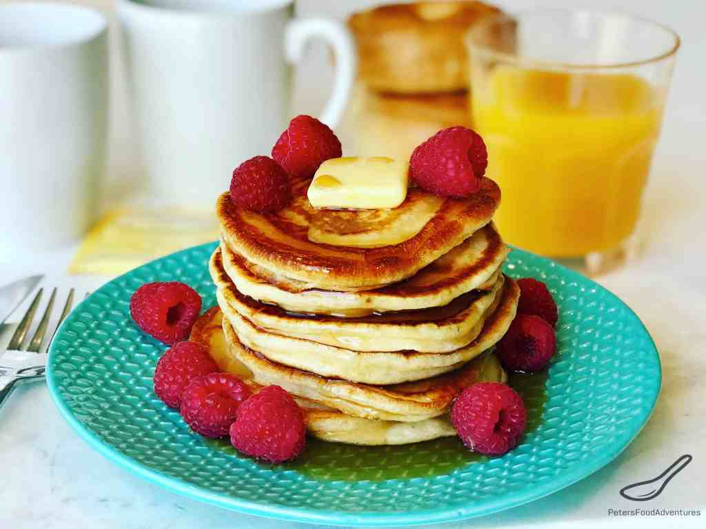 Pancake stack with fresh raspberries and maple syrup