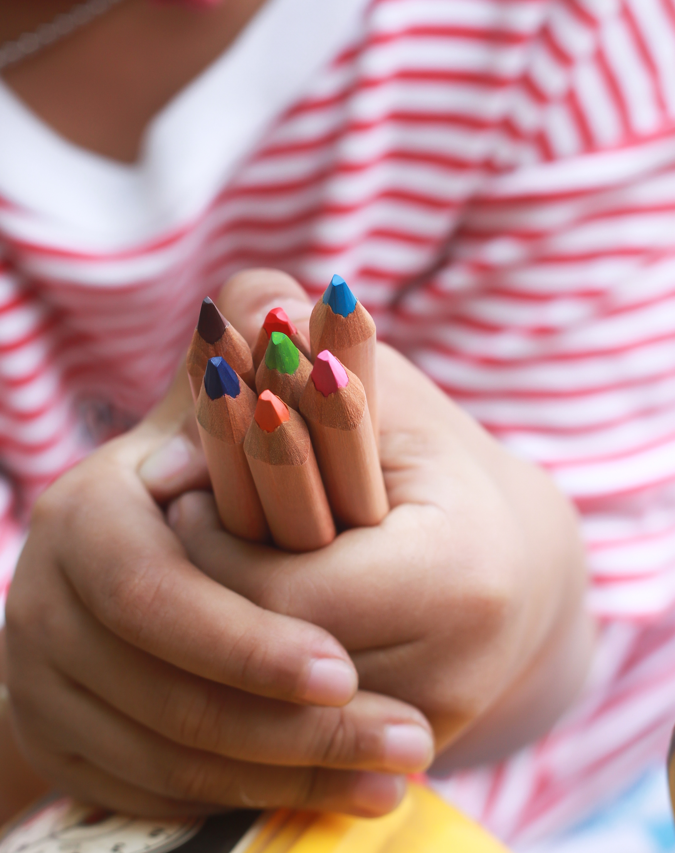 A child hold color pencils with a little hand