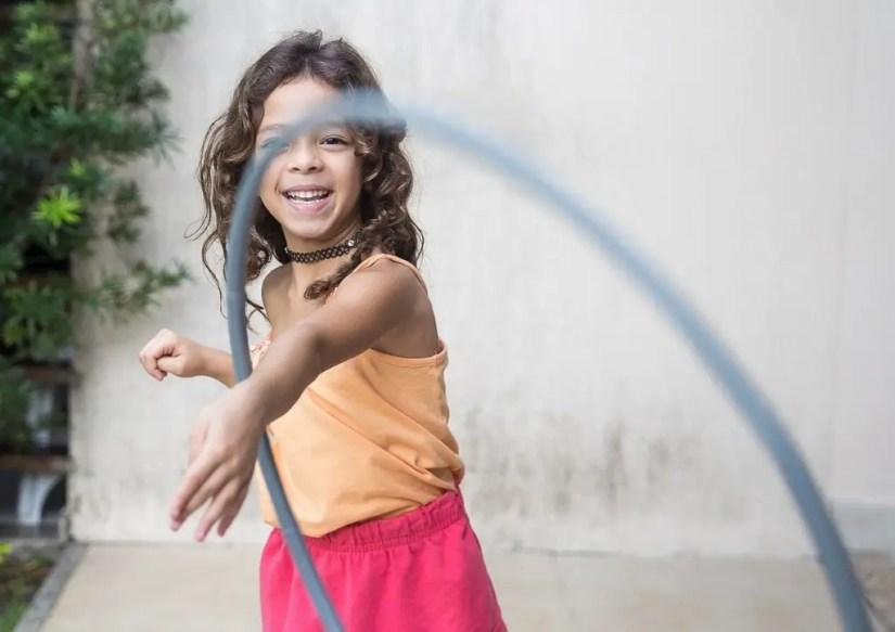 Petite fille jouant avec un cerceau au hula hop, un jeu de plein air qui se joue seul.