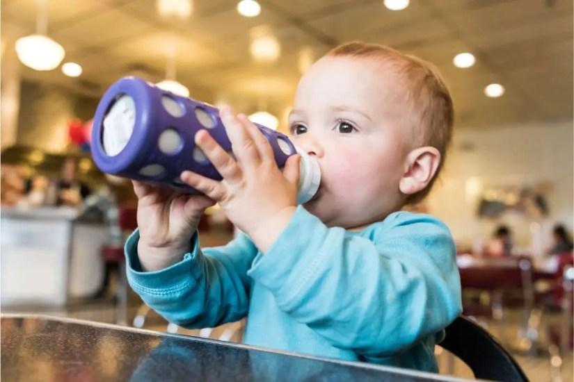 Bébé tenant un biberon protégé par un étuis en silicone
