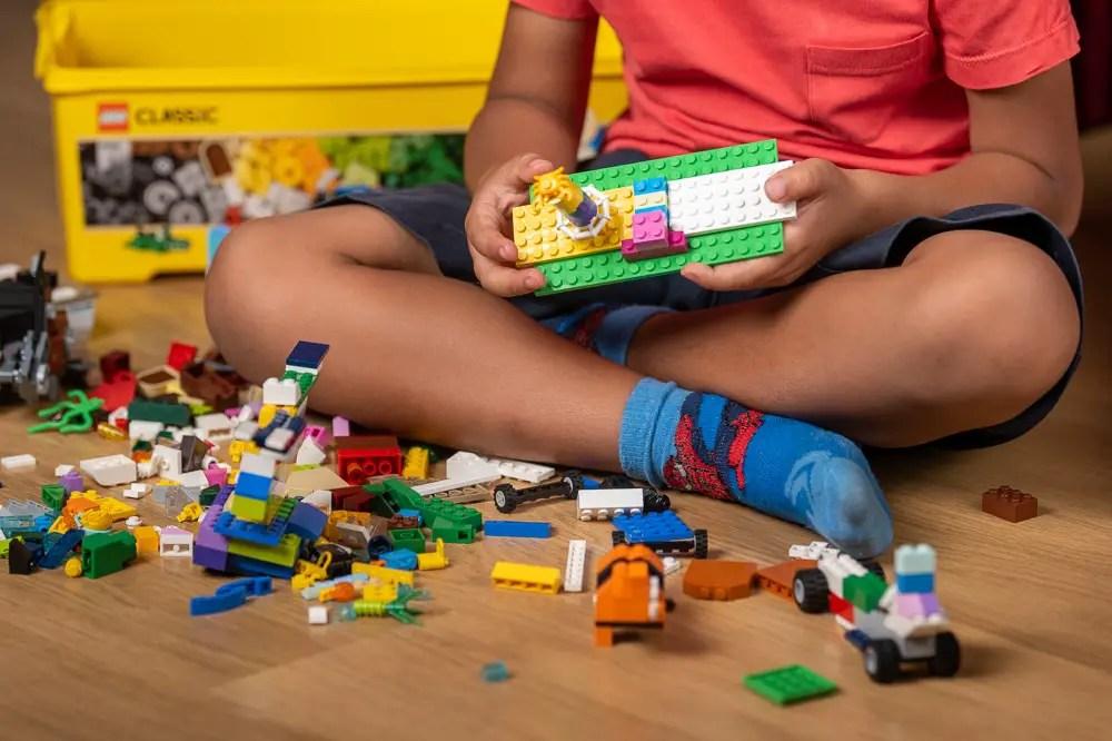 Enfant jouant avec une boîte de briques Lego
