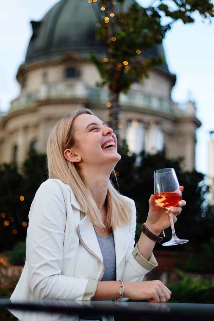 laughing woman drinking wine in street restaurant