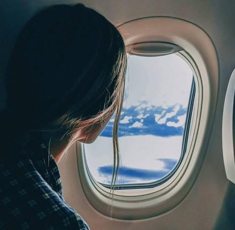 femme qui regarde par le hublot de l'avion