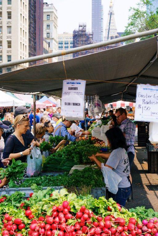 étales de légumes et des gens sur le marché