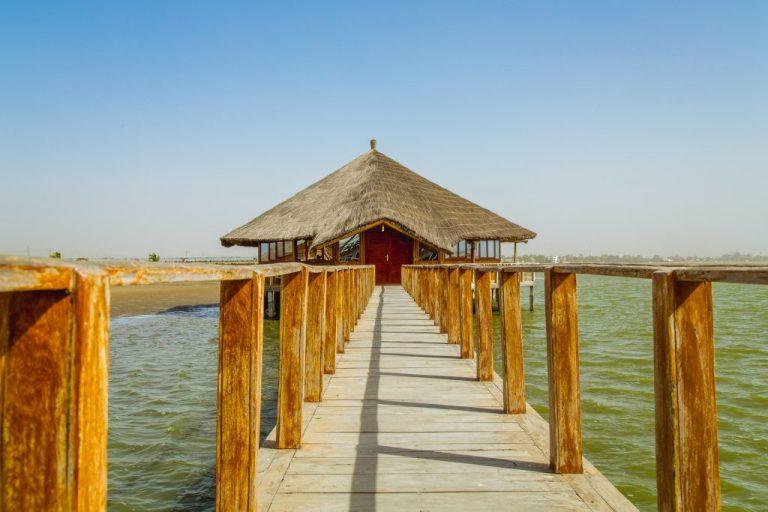 Sénégal pont au dessus eau verte pour rejoindre maison sur pilotis