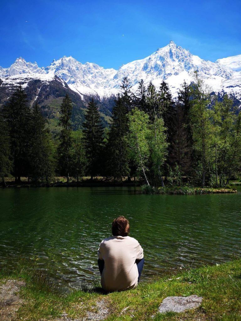 homme assis au bord d'un lac vert avec arbre et montagne