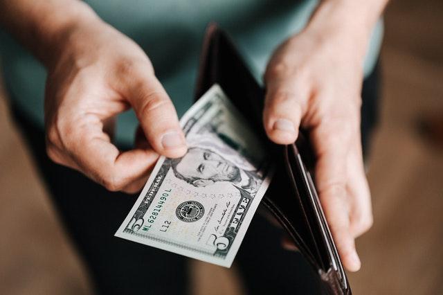 billet dans un portefeuille que tient un homme
