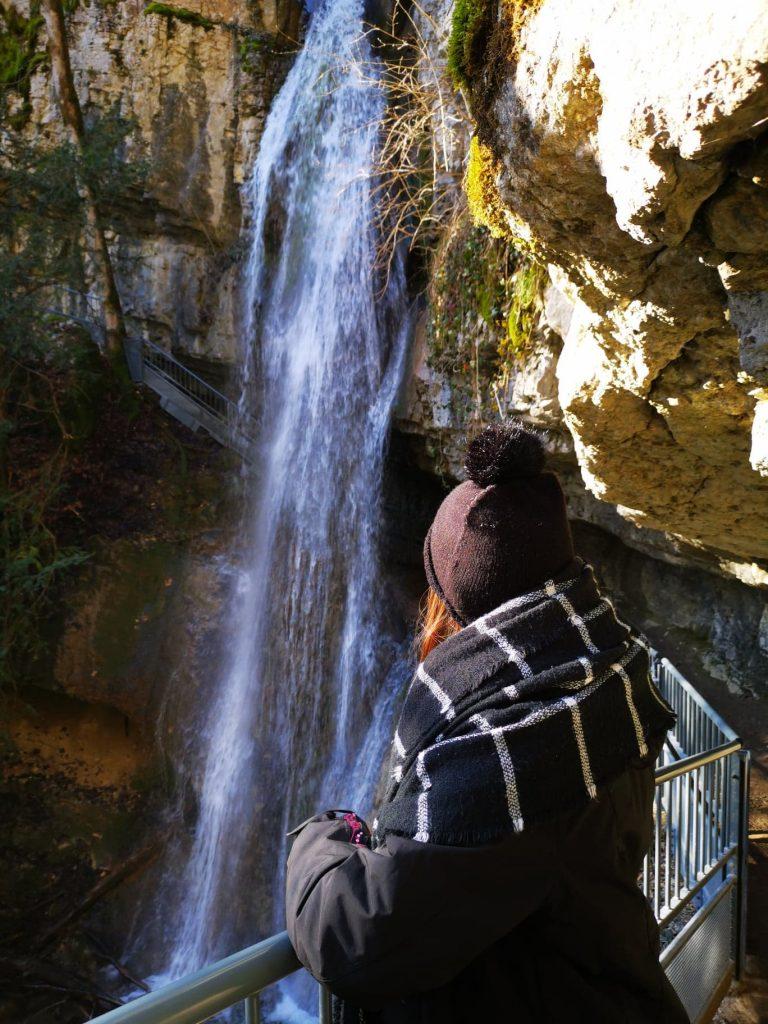 femme avec un bonnet qui regarde la cascade