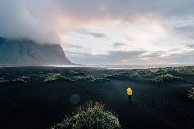 Islance : sable noir, une personne avec un manteau jaune qui observe paysage
