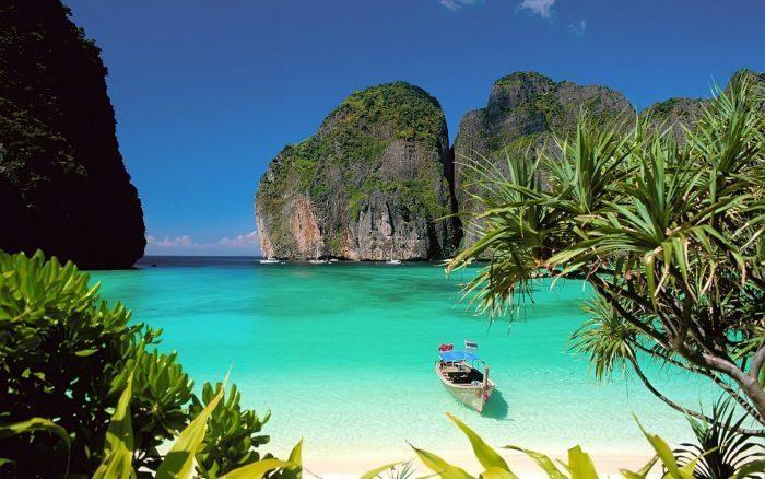 barque sur eau turquoise et falaise verdoyante à ko phi phi