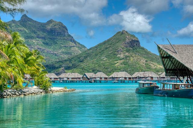 maisons sur pilotis et falaises verdoyantes à Tahiti